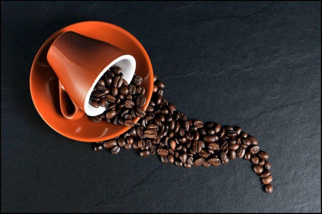 Café com blockchain: desvendando o caminho do grão à taça de café. Imagem com fundo preto, caneca vermelha derramando grãos de café na superfície.